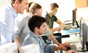 Students with teacher in front of desktop computer; Shutterstock ID 96602677; PO: Shutterstock; Job: Shutterstock Groupon global relicense 5000