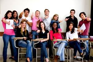friends or university students smiling in a classroom with thumbs up